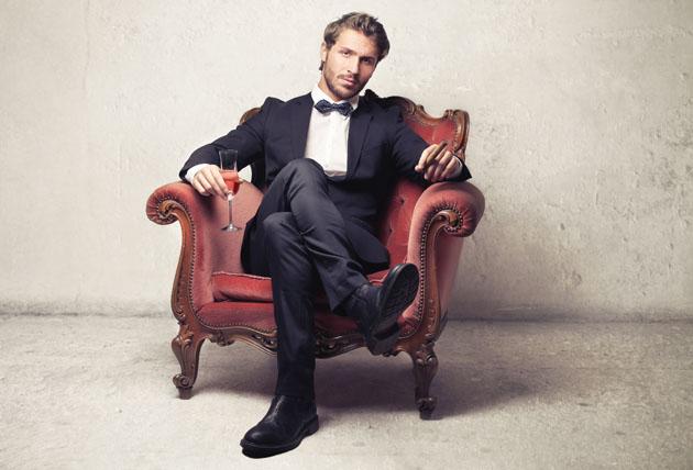 DGXGK6 Gentleman sitting on a vintage armchair
